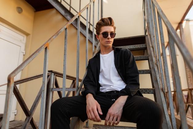 철 계단에 앉아 우아한 젊은 hipster 남자. 매력적인 남자 모델