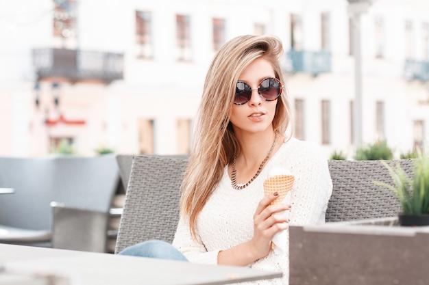 세련된 선글라스에 니트 흰색 스웨터에 금발 머리를 가진 우아한 젊은 힙 스터 여자는 카페에 앉아 여름 날에 달콤한 아이스크림을 먹고 있습니다. 휴가에 아름 다운 소녀입니다.