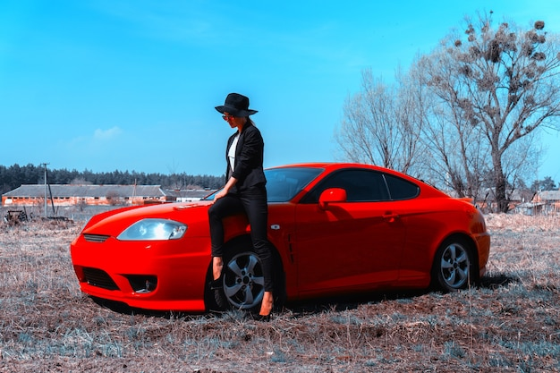 Elegant young lady in hat with wide brim sits on a red sport car in the field Premium Photo