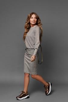 Элегантная молодая дама в повседневной одежде и кроссовках смотрит в сторону и позирует на сером фоне изолированно.