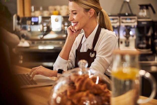 카페에서 컴퓨터에서 일하는 우아한 젊은 여성