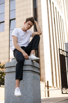 Elegant young man in a fashionable black shirt in a white stylish t-shirt in black pants with a trendy hairstyle rests near a modern business center. attractive guy in the street on a summer day.