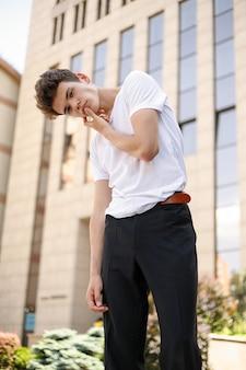 세련된 검은색 셔츠를 입은 우아한 청년은 세련된 흰색 티셔츠에 검은색 바지에 트렌디한 헤어스타일을 하고 현대적인 비즈니스 센터 근처에 있습니다. 여름날 거리에서 매력적인 남자.