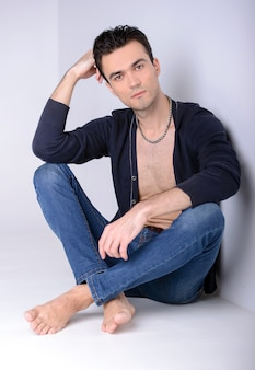 Elegant young man is sitting on floor and posing.