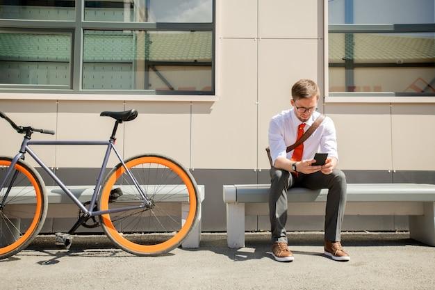 現代のビジネスセンターの壁や窓にベンチに座ってスマートフォンでエレガントな若い男メッセージ