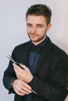 Элегантный молодой человек в костюме и галстуке-бабочке. ножницы в руках.