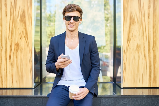 Elegant young man posing with smartphone