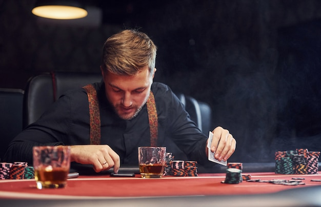 Elegant young man sits in casino, using phone and plays poker game