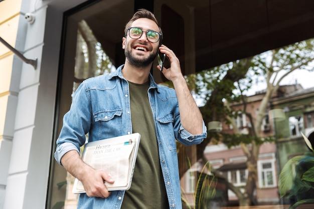 新聞とノートパソコンを手に街の通りを歩きながらスマートフォンで話している眼鏡をかけているエレガントな若い男