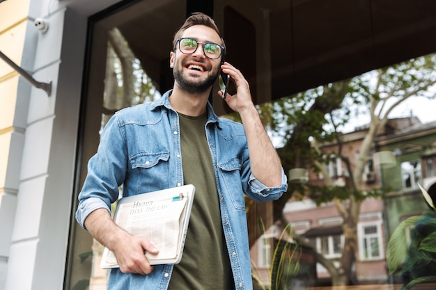 Elegant young man wearing eyeglasses talking on smartphone while walking through city street with newspaper and laptop in hand