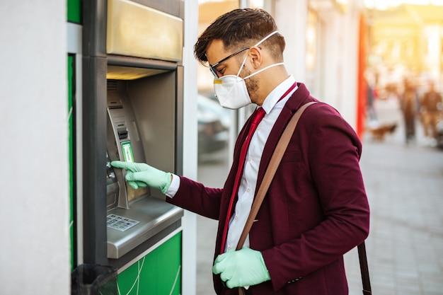 보호 마스크를 쓴 우아한 청년이 도시 거리에 서서 보호 장갑을 낀 atm 기계를 사용합니다. 바이러스 전염병 예방 및 의료 개념.