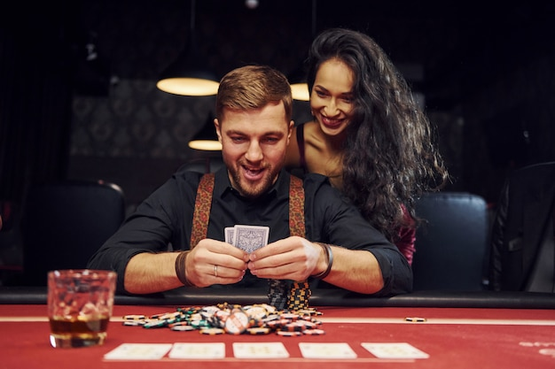 Elegant young man with woman before him is sitting and celebrating vitory in casino by playing poker game