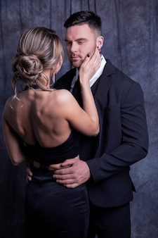 Elegant young man and woman tenderly embrace each other enjoying the moment