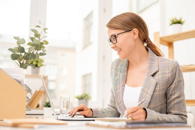 Elegant young office manager making working notes while looking through online data in front of laptop