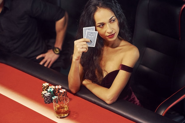 Elegant young people sits by table and playing poker in casino