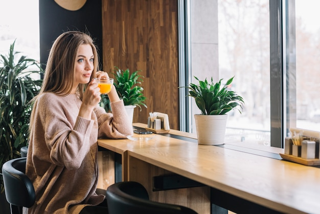 Elegant young positive woman holding cup of drink at bar counter near window in cafe