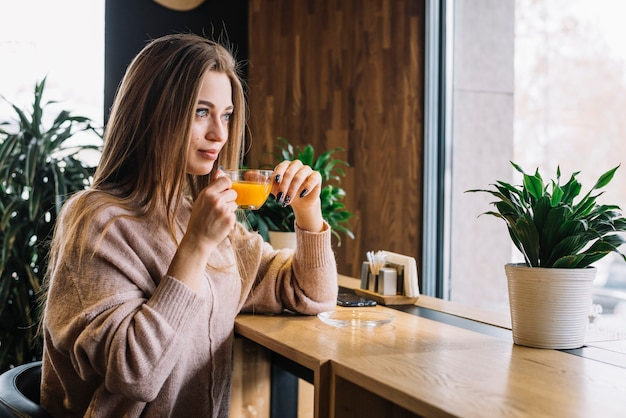 Elegant young positive woman holding mug of drink at bar counter near window in cafe