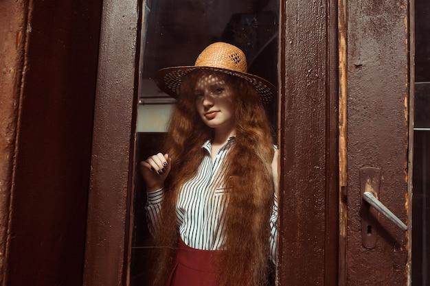 彼女の顔に影のある麦わら帽子のエレガントな若い赤い髪のモデル