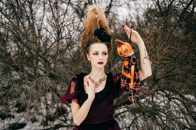 Elegant young red-haired woman with unusual hairstyle wearing wine-colored dress and holding halloween pumpkin