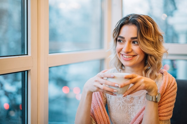 Elegant young smiling woman with cup of drink near window in cafe