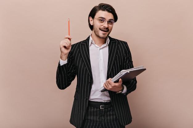 갈색 머리를 가진 우아한 젊은 교사, 세련된 가벼운 셔츠, 검은색 줄무늬 양복, 안경을 쓰고 글을 쓰고 펜을 들고 강의를 하고 있습니다.