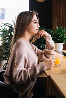 Elegant young thoughtful woman with cup of drink at bar counter in cafe