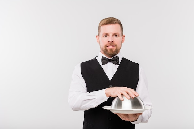 Elegant young waiter in bowtie and black waistcoat holding cloche with food for one of clients of restaurant