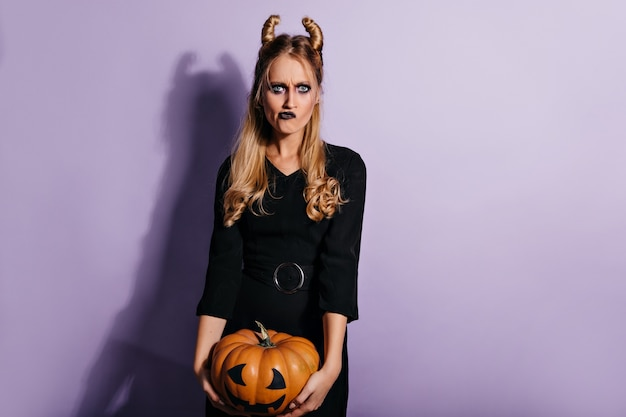 Элегантная молодая ведьма, держащая тыкву хеллоуина. грустная девушка-вампир с темным макияжем позирует на фиолетовой стене.