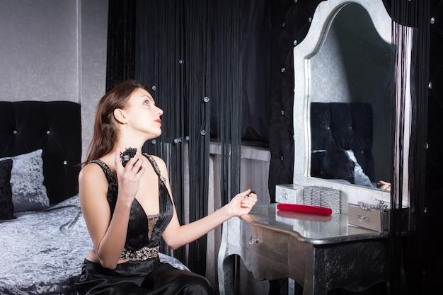 彼女はスタイリッシュなグレーと白の寝室の彼女のドレッシングテーブルで鏡の前に座って香水を適用するエレガントな若い女性