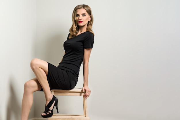 Elegant young woman blond in black dress