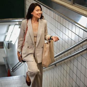 Elegante giovane donna che esce dalla stazione della metropolitana