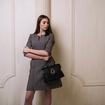 Elegant young woman in dress with crossed hands and handbag in room