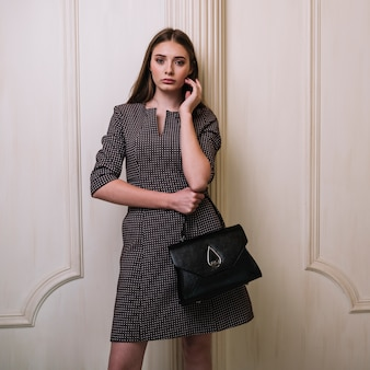 Elegant young woman in dress with handbag holding cheek in room