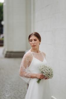 La giovane donna elegante in vestito bianco alla moda sta vicino alla parete