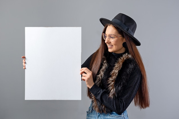 Elegant young woman in glasses and hat showing empty board banner, isolated on gray, copy space