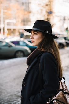 Elegant young woman in hat and coat on street