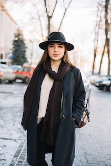 Elegant young woman in hat and coat with scarf on street