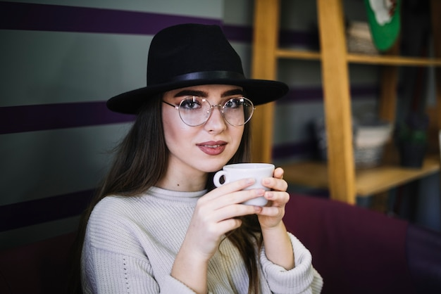 Elegant young woman in hat and eyeglasses with mug of drink
