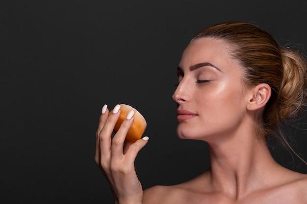 オレンジを保持しているエレガントな若い女性