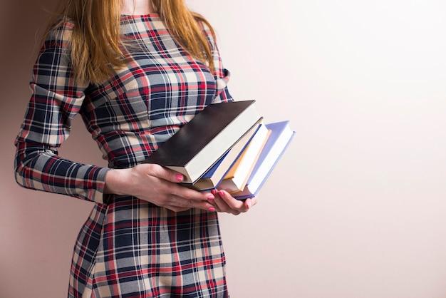 いくつかの書籍を保持しているエレガントな若い女性