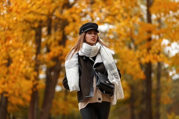 秋の日に公園で金箔と木の背景にポーズをとるスカーフと革のバッグとスタイリッシュな茶色のジャケットでシックな帽子をかぶったエレガントな若い女性。屋外の美しい少女。