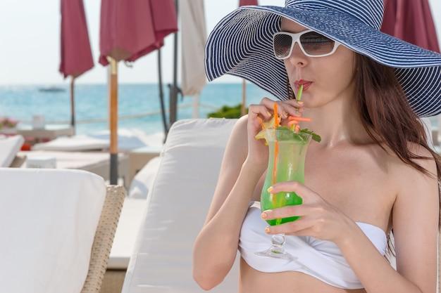 彼女は海辺のリゾートでリクライニングチェアでリラックスしながら、トロピカルカクテルをすすりながらわらの日よけ帽とサングラスでエレガントな若い女性