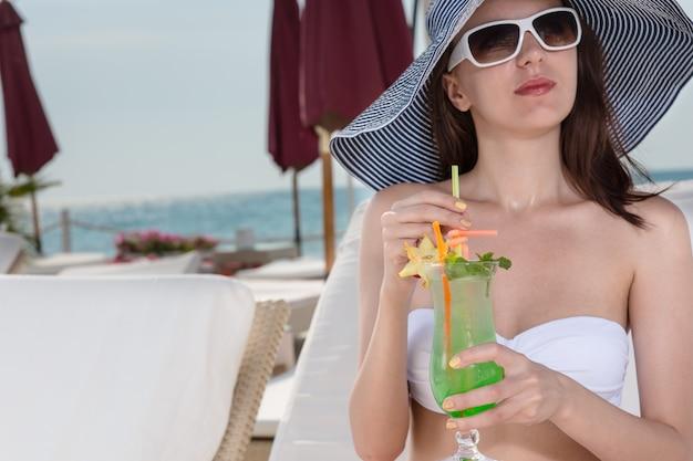 トレンディな日よけ帽とサングラスをかけたエレガントな若い女性が、夏休みに高級リゾートのビーチでリラックスしながらトロピカルカクテルを飲みます。