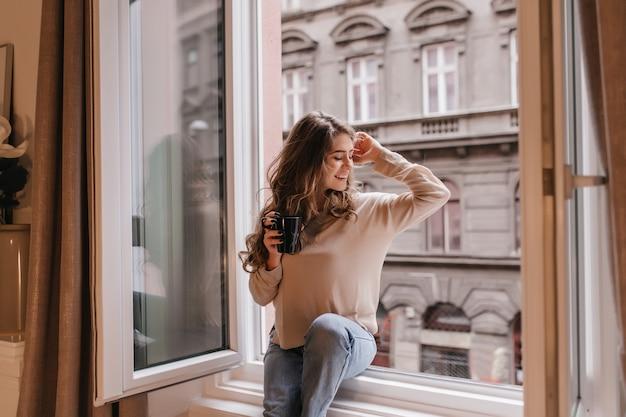 Элегантная молодая женщина в бежевой рубашке сидит на подоконнике и смотрит на город