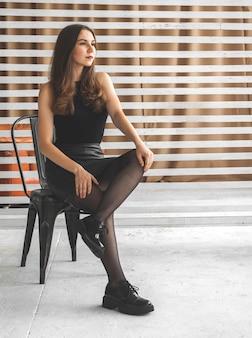검은 옷, 드레스, 팬티 스타킹, 부츠를 입은 우아한 젊은 여성이 스튜디오 배경의 의자에 앉아 있습니다. 미래와 도시 패션 컨셉 사진