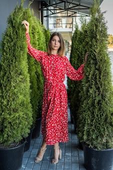 Элегантная молодая женщина в модном красном платье на природе, летнее время