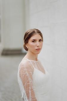 Элегантная молодая женщина в модном белом платье стоит у стены