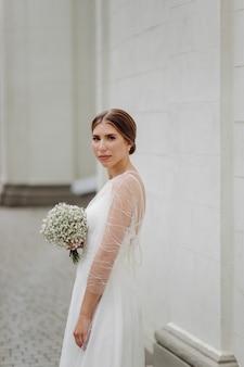 세련된 흰색 드레스를 입은 우아한 젊은 여성이 벽 근처에 서 있습니다.