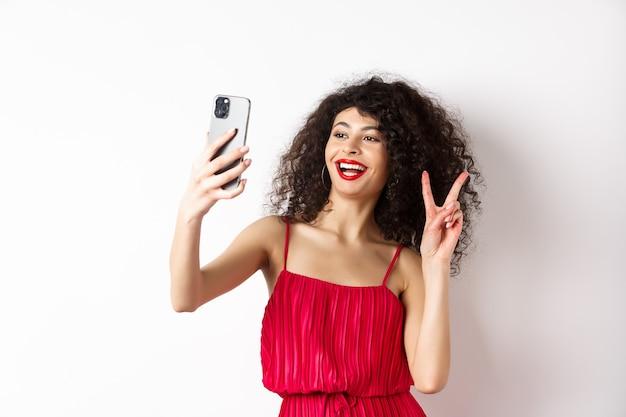 スマートフォンでselfieを取り、イベントパーティーでポーズをとって、白い背景の上の携帯電話で立っている赤いドレスのエレガントな若い女性。