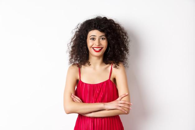 化粧をした赤いドレスを着たエレガントな若い女性、お祝いイベントのドレスアップ、カメラで幸せな笑顔、白い背景の上に立っています。